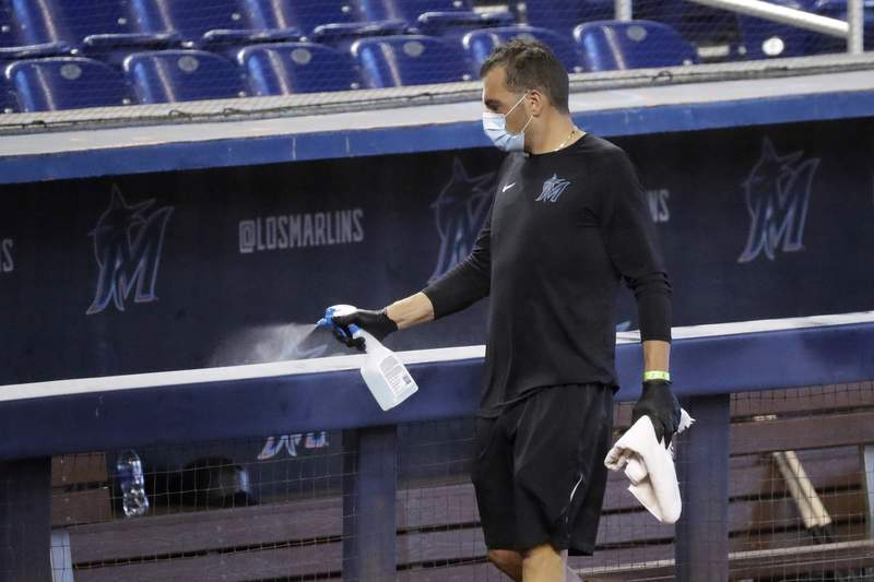 In this July 16 file photo, a worker sprays the dugout rail to help prevent the spread of the coronavirus, before the Miami Marlins' baseball practice at Marlins Park.