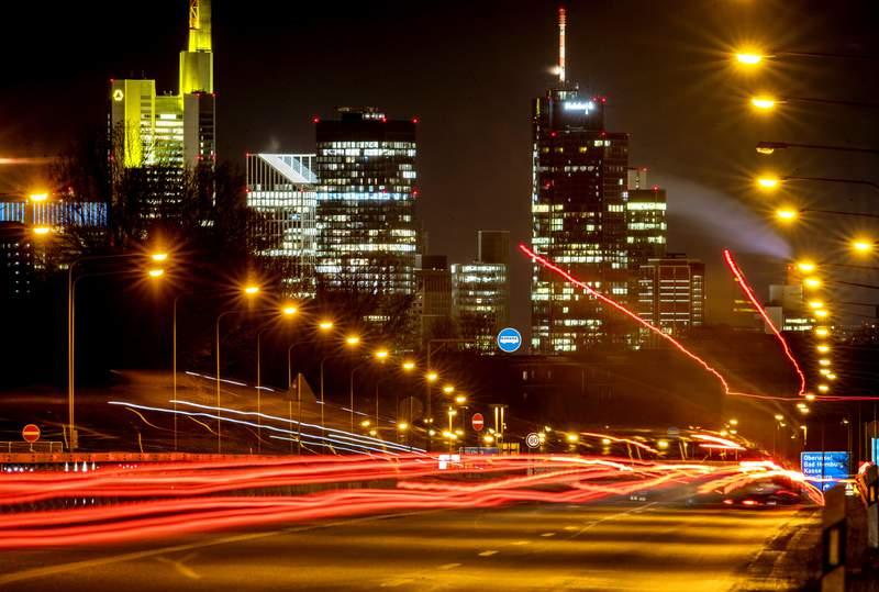 Long time exposure photo shows commuters driving towards Frankfurt, Germany, Thursday, Jan. 14, 2021. In background the buildings of the banking district. (AP Photo/Michael Probst)