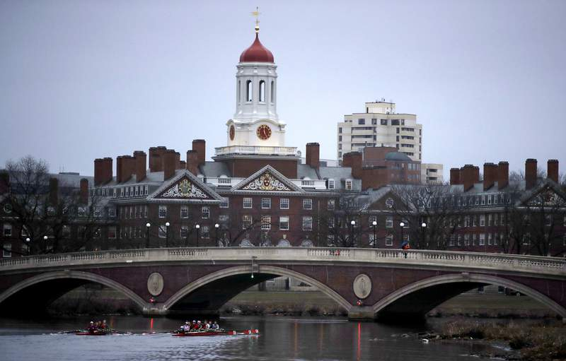 FILE - In this March 7, 2017 file photo, rowers paddle down the Charles River past the campus of Harvard University in Cambridge, Mass. An annual survey finds that most U.S. universities made money on their financial investments last year, but their returns were tempered by a global economic slowdown fueled by Americas trade war with China. Harvard University remained the wealthiest school in the U.S., with an endowment valued at nearly $40 billion.  (AP Photo/Charles Krupa, File)