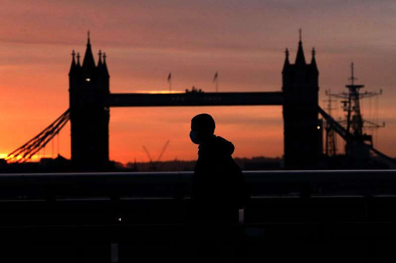 """A person wearing a face mask to try to stop the spread of coronavirus walks across London Bridge, with Tower Bridge in the background, at sunrise in London, Monday, Oct. 12, 2020. In response to the coronavirus' resurgence, British Prime Minister Boris Johnson is expected to announce in Parliament on Monday a three-tier local lockdown system, formally known as """"Local COVID Alert Levels,"""" for England, his office said. (AP Photo/Matt Dunham)"""