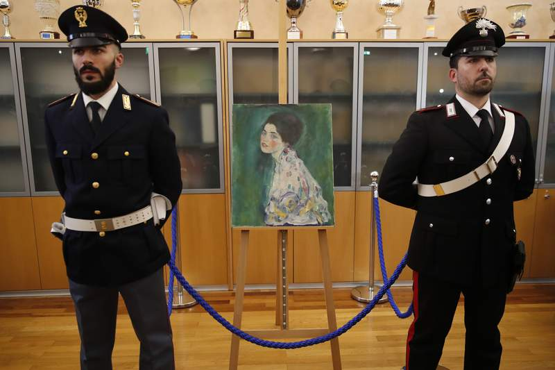 """FILE - In this Friday, Jan. 17, 2020 file photo, an Italian Policeman, left, and a Carabiniere, paramilitary police officer, stand beside a painting which was found last December near an art gallery and believed to be the missing Gustav Klimt's painting 'Portrait of a Lady' during a press conference in Piacenza, Italy. Gustav Klimt's """"Portrait of a Lady,"""" which was missing for nearly 23 years after its theft from an Italian museum, will be a star in an exhibit about the artist that is opening this month at a Rome museum. (AP Photo/Antonio Calanni)"""