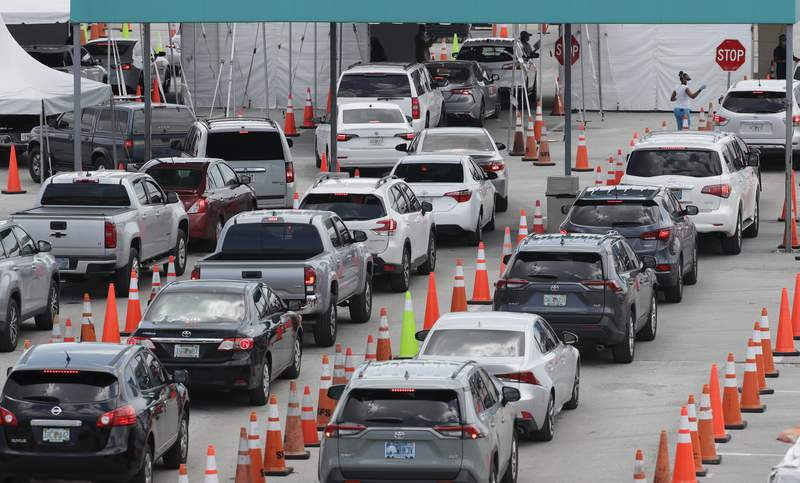Cars wait in line at a drive-thru COVID-19 testing site outside Hard Rock Stadium earlier this month.