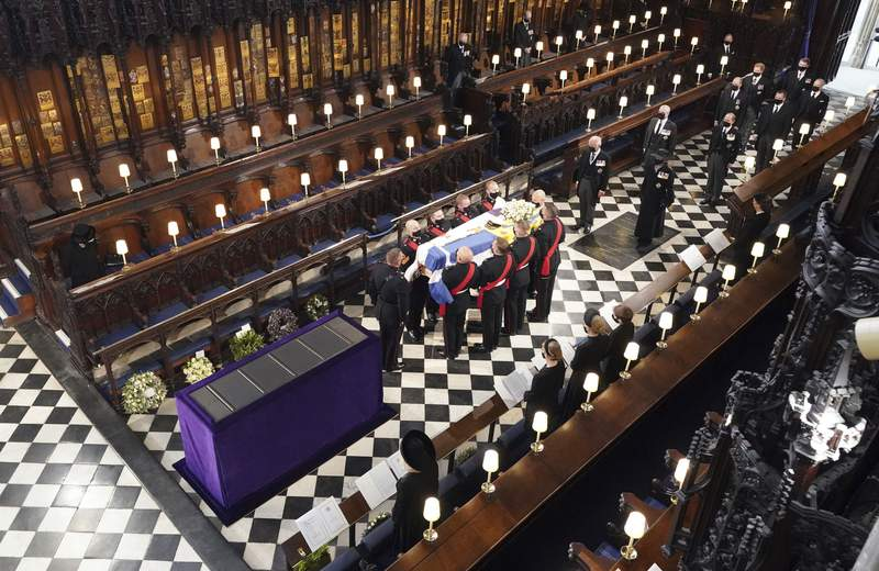 Britain's Queen Elizabeth watches as pallbearers carry the coffin of the Duke of Edinburgh during his funeral at St George's Chapel in Windsor Castle, Windsor, England, Saturday April 17, 2021. Prince Philip died April 9 at the age of 99 after 73 years of marriage to Britain's Queen Elizabeth II. (Dominic Lipinski/Pool via AP)
