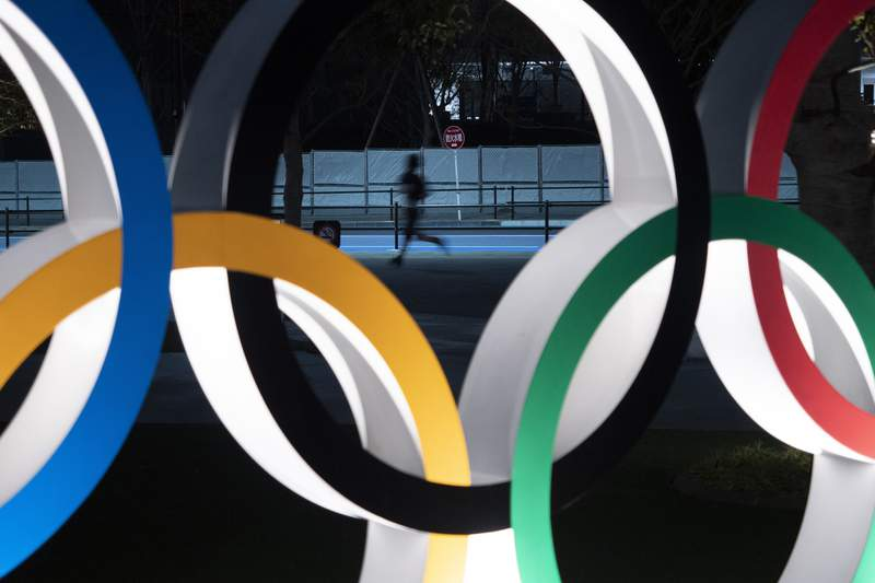 FILE - In this March 30, 2020, file photo, a man jogs past the Olympic rings in Tokyo. Tokyo Olympic CEO Toshiro Muto talked Thursday, May 21, about the need to take countermeasures to combat COVID-19 at next year's postponed games.  (AP Photo/Jae C. Hong, File)