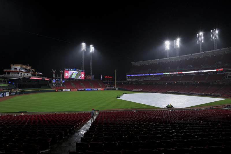 A trap covers the infield during a rain delay in the eighth inning of a baseball game between the Arizona Diamondbacks and the Cincinnati Reds in Cincinnati, Tuesday, April 20, 2021. (AP Photo/Aaron Doster)