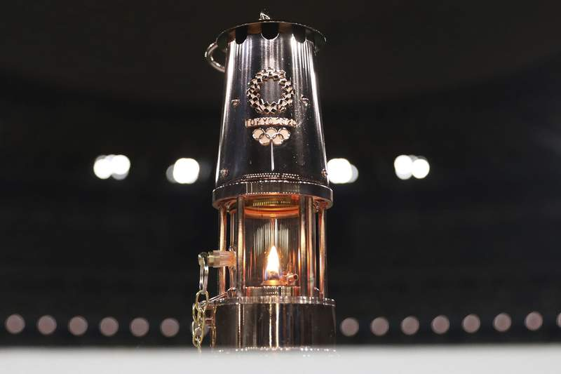 """FILE - This July 23, 2020, file photo shows the Olympic flame in a lantern, after the """"One Step Forward - +1 Message - TOKYO 2020"""" video message unveiling event at the Olympic Stadium, in Tokyo. The Olympic flame is going on display in Tokyo, just a short walk from the new National Stadium where it was supposed to be burning a month ago. The flame arrived in Japan from Greece in March and has been largely hidden away in Tokyo since the Olympics were postponed by the COVID-19 pandemic until next year. The flame is scheduled to be unveiled on Monday, Aug. 31, 2020, at a small ceremony with Yoshiro Mori, the president of the Tokyo Olympic organizing committee, and Yasuhiro Yamashita, the president of the Japanese Olympic Committee.(Du Xiaoyi/Pool Photo via AP)"""