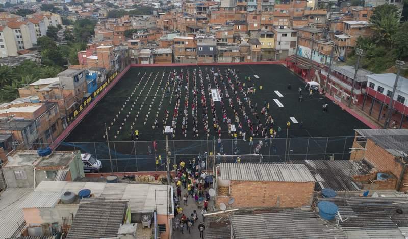 """ARCHIVO - En esta foto del 26 de abril del 2021, residentes esperan en una ancha de ftbol para recibir comida donada por la organizacin local sin fines de lucro """"G10 Favelas"""", en medio de la pandemia de coronavirus, en el rea de Capao Redondo, en Sao Paulo, Brasil.  (AP Foto/Andre Penner)"""
