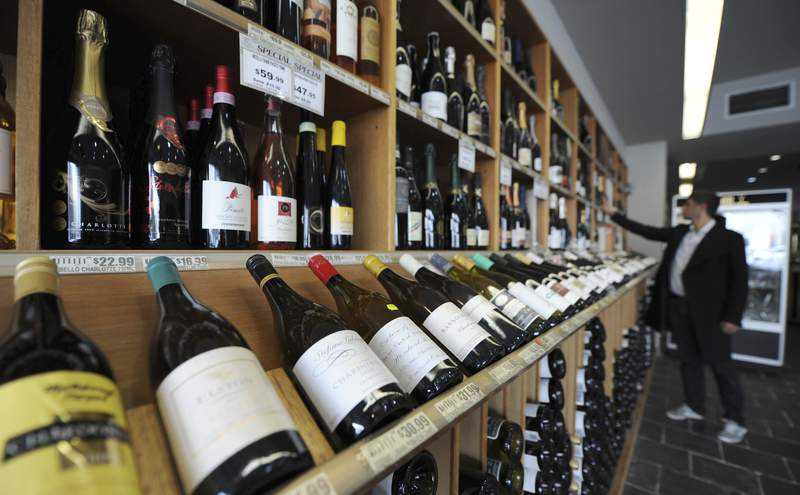 In this Feb. 29, 2012, file photo a shopper looks over the wine at King & Godfree, one of Australia's oldest licensed grocery stores in, Melbourne, Australia. China on Tuesday, Aug. 18, 2020, began investigating whether Australia is dumping wine in a trade dispute that further strains relations between the countries and could shut the biggest export market for Australian wine. (AP Photo/Mal Fairclough, FILE)