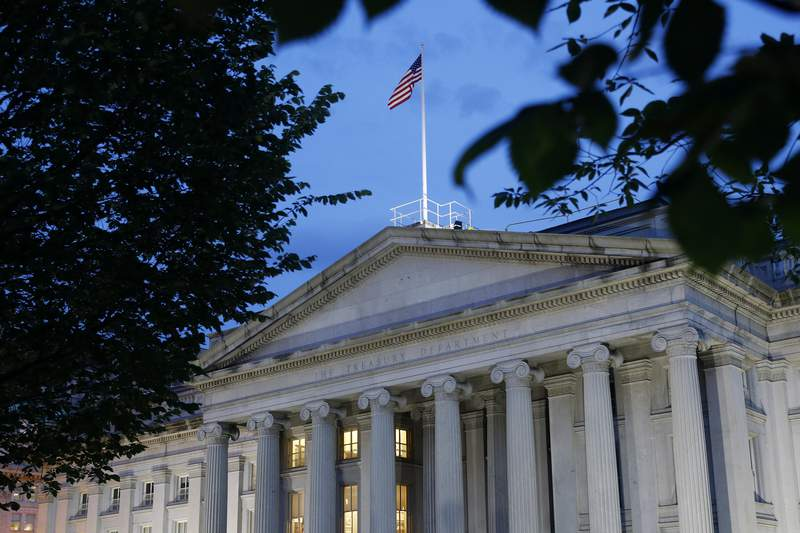 FILE - This Thursday, June 6, 2019, file photo shows the U.S. Treasury Department building at dusk, in Washington. The Treasury Department said Wednesday, March 24, 2021, that it has sent out another 37 million economic impact payments, bringing the total disbursed in the past two weeks to $325 billion. (AP Photo/Patrick Semansky, File)