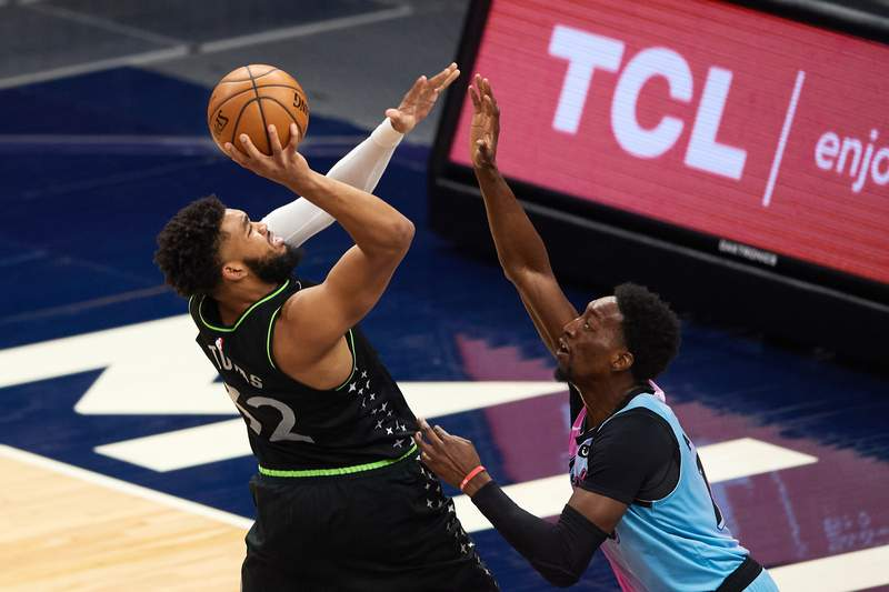 Karl-Anthony Towns of the Minnesota Timberwolves shoots the ball against Bam Adebayo of the Miami Heat during the third quarter of the game at Target Center on April 16, 2021 in Minneapolis, Minnesota. The Timberwolves defeated the Heat 119-112.