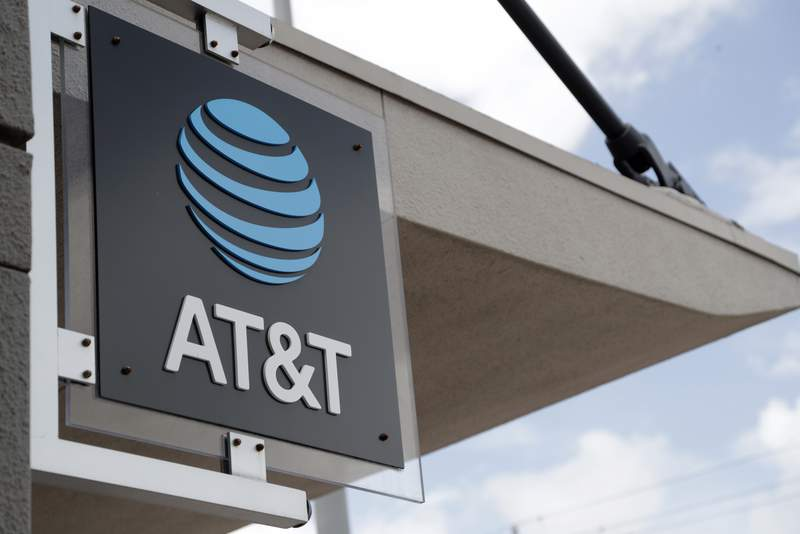 FILE - In this July 18, 2019 photo, a sign is displayed at an AT&T retail store in Miami.  Shares of AT&T Inc. rose Thursday, April 22, 2021 after the telecom giants first-quarter results topped analyst expectations.  (AP Photo/Lynne Sladky, File)