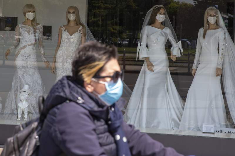 A cyclist wearing a protective mask to protect against coronavirus rides past a wedding dress store with mannequins wearing face masks, in Zagreb, Croatia, Thursday, April 23, 2020. The store is closed because of Covid-19 lockdown. (AP Photo/Darko Bandic)