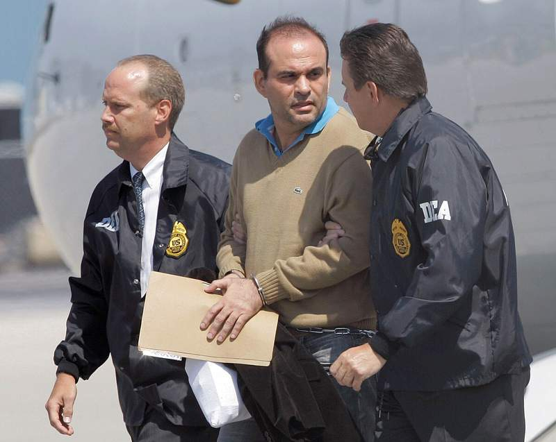 FILE - In this May 13, 2008 file photo, Colombian paramilitary warlord Salvatore Mancuso is escorted by U.S. DEA agents upon his arrival to Opa-locka, Florida. A legal battle is quietly brewing in the U.S. in 2020 over Colombias request that this former paramilitary warlord be sent home after completing his drug sentence in the U.S. (AP Photo/Alan Diaz, File)