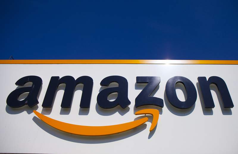 FILE - In this Thursday, April 16, 2020, file photo, the Amazon logo is seen in Douai, northern France. Amazon started selling a wrist band Thursday, Aug. 27, 2020, that tracks workouts, sleep and body fat. It can also listen to your voice all day and tell you when you sounded happy or sad. (AP Photo/Michel Spingler, File)