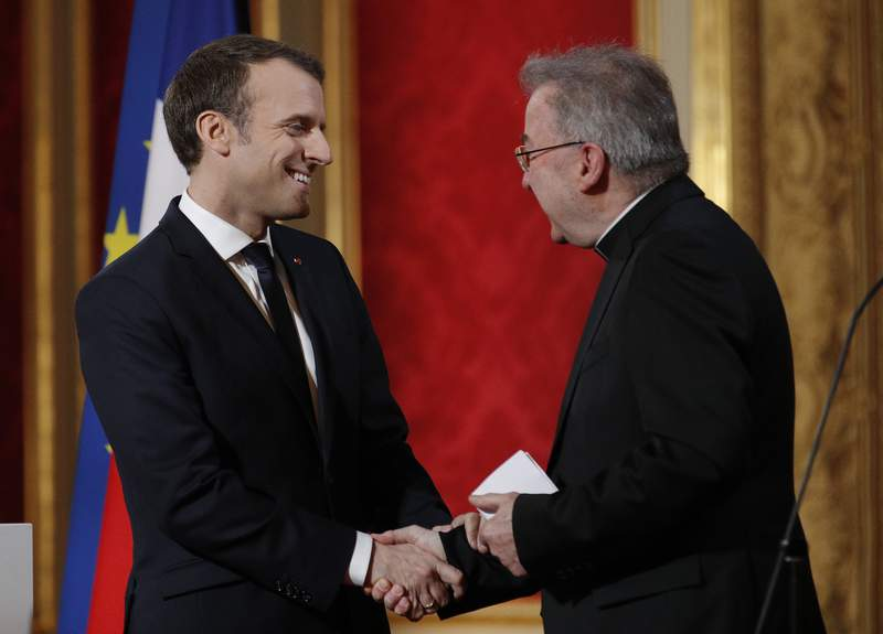 FILE - In this Jan.4, 2018 file photo, French President Emmanuel Macron, left, greets Apostolic Nuncio to France Luigi Ventura, at the Elysee Palace in Paris. Multiple men have accused Archbishop Luigi Ventura of groping and inappropriate touching, and the Vaticans former ambassador to France goes on trial Tuesday Nov. 10, 2020, for alleged sexual misconduct. (Yoan Valat, Pool via AP, File)