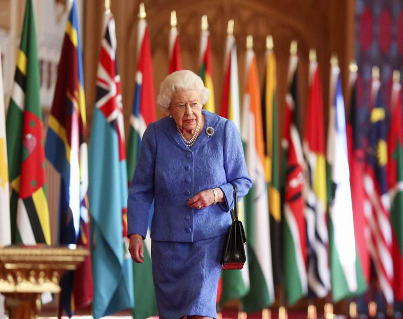Britain's Queen Elizabeth II walks past Commonwealth flags in St George's Hall at Windsor Castle, England to mark Commonwealth Day in this image that was issued on Saturday March 6, 2021. The timing couldnt be worse for the Queen's grandson Harry and his wife Meghan. The Duke and Duchess of Sussex will finally get the chance to tell the story behind their departure from royal duties directly to the public on Sunday, when their two-hour interview with Oprah Winfrey is broadcast. (Steve Parsons/Pool via AP)