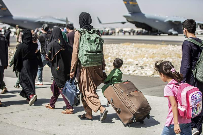 FILE - In this Aug. 24, 2021, file photo provided by the U.S. Marine Corps, families walk towards their flight during ongoing evacuations at Hamid Karzai International Airport, in Kabul, Afghanistan. More than 30 California children are stuck in Afghanistan after traveling to the country to see their relatives weeks before the Taliban seized power and US forces left, according to school districts where the kids are enrolled. (Sgt. Samuel Ruiz/U.S. Marine Corps via AP, File)