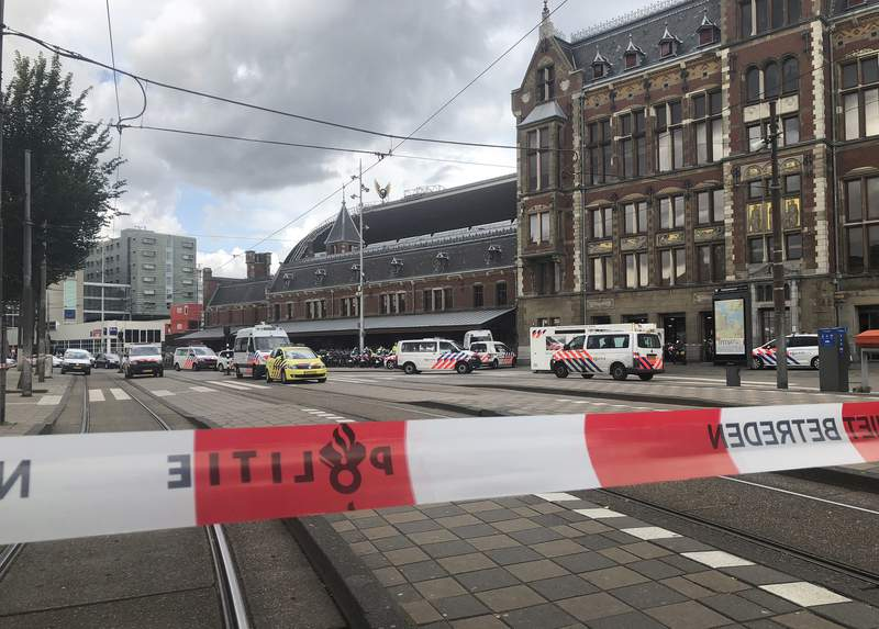 FILE - In this Friday Aug. 31, 2018 file photo, Dutch police officers near the scene of a stabbing attack at central station in Amsterdam, the Netherlands. An Amsterdam appeals court on Monday, Nov. 16, 2020 upheld the terror attack conviction of an Afghani asylum seeker who stabbed two American tourists, seriously injuring them, at Amsterdams main railway station in 2018. The court said in a statement that judges slightly reduced the sentence of the attacker, who has been identified only as Jawed S., from nearly 27 years to 25 years based on sentences in similar cases and on his young age. (AP Photo/Aleks Furtula, File)