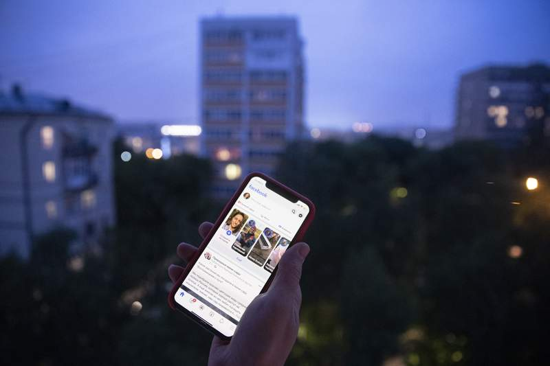 A user holds a smartphone with an opened Facebook page in Moscow, Russia, Thursday, June 10, 2021. Russian authorities have ordered Facebook and messaging app Telegram to pay steep fines for failing to remove banned content. The move could be part of growing Russian efforts to tighten control over social media platforms. A Moscow court fined Facebook a total of 17 million rubles (roughly $236,000) and Telegram 10 million rubles ($139,000). (AP Photo/Pavel Golovkin)