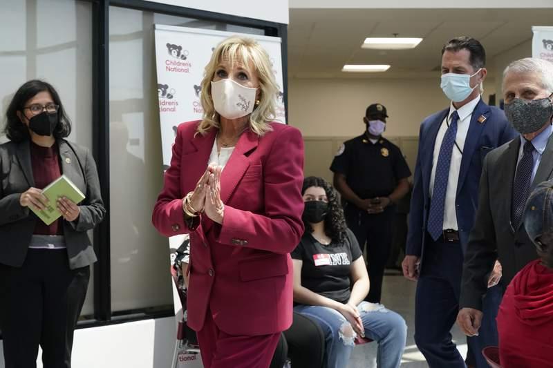 La primera dama Jill Biden hace un gesto con las manos el jueves 20 de mayo de 2021 durante un recorrido por un sitio de vacunacin contra el COVID-19, en Washington. A la extrema derecha est el doctor Anthony Fauci, director del Instituto Nacional de Alergias y Enfermedades Infecciosas. (AP Foto/Jacquelyn Martin)