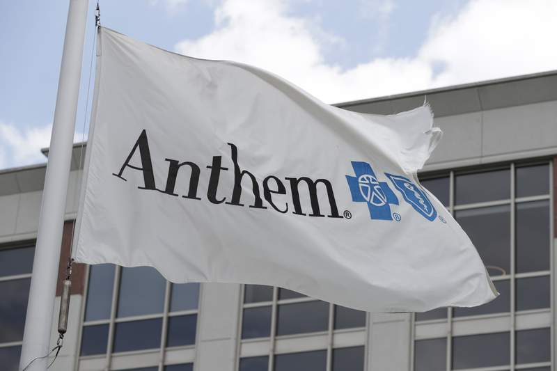 FILE - In this May 14, 2019, file photo a flag flies outside the corporate headquarters building of health insurance company Anthem in Indianapolis. Anthem delivered a better-than-expected first quarter and pushed its 2021 forecast past expectations, as growing enrollment and a pharmacy benefits business helped the health insurer. The Blue Cross-Blue Shield insurer said Wednesday, April 21, 2021, that it now expects full-year earnings to come in at greater than $25.10 per share.  (AP Photo/Michael Conroy, File)