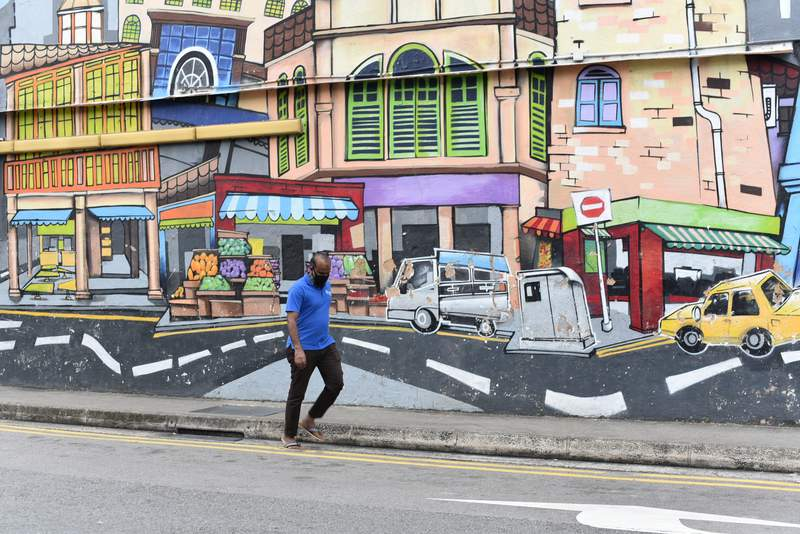 A man with a facemask walks past a wall mural in Singapores Little India district on Saturday, May 16, 2020. Wearing of facemarks is mandatory for everyone who goes outside their homes to control the spread of the coronavirus in the city state. Singapore has reported more than 27,000 COVID-19 cases, with 90% of the cases linked to foreign workers dormitories, but it has a low fatality rate of 21 deaths. (AP Photo/YK Chan)