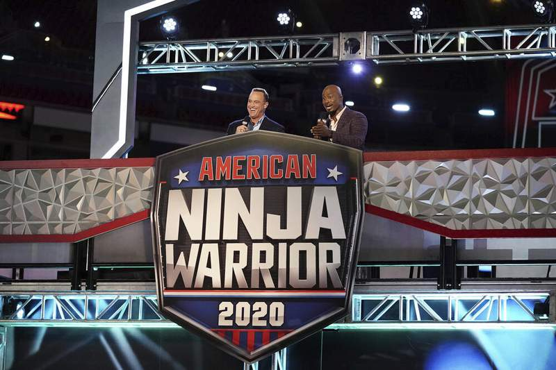 """This image released by NBC shows hosts Matt Iseman, left, and Akbar Gbajabiamila on the set of """"American Ninja Warrior."""" Young TV viewers may be getting the message that fame is less important than values like achievement and a sense of community. That's according to a new study from the University of California, Los Angeles. In examining the TV shows most popular with children ages 8 to 12, knowns as tweens, researchers found that the emphasis on fame diminished in 2017. (Elizabeth Morris/NBC via AP)"""