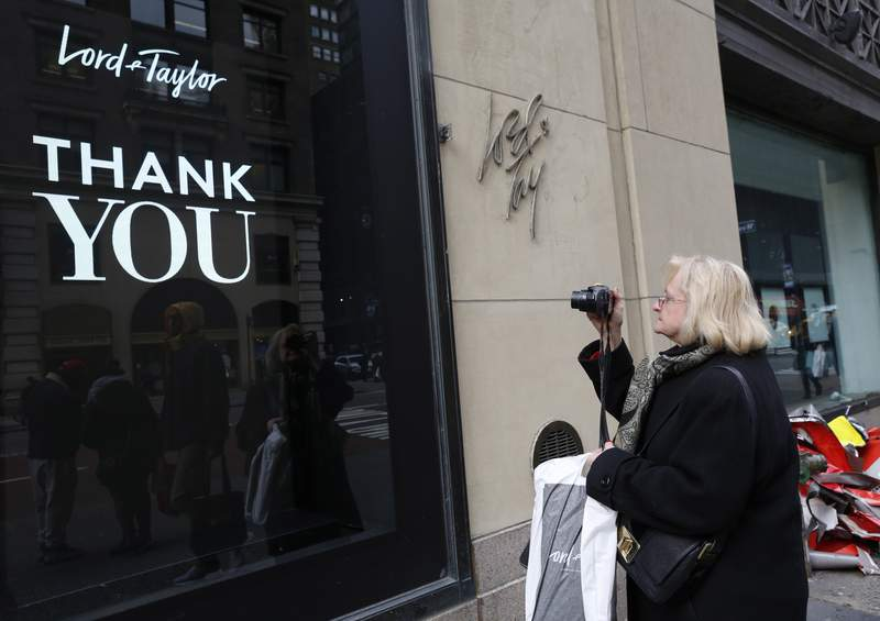 FILE - In this Jan. 2, 2019 file photo, a woman, who declined to give her name, pauses to take a photo of a sign outside Lord & Taylor's flagship Fifth Avenue store which closed its doors for good after a months-long blowout sale, in New York. Lord & Taylor, one of the countrys oldest department stores, is going out of business after filing for bankruptcy earlier this month. It will close its remaining 38 stores and shut down its website, the company said Thursday, Aug. 27, 2020.   (AP Photo/Kathy Willens, File)