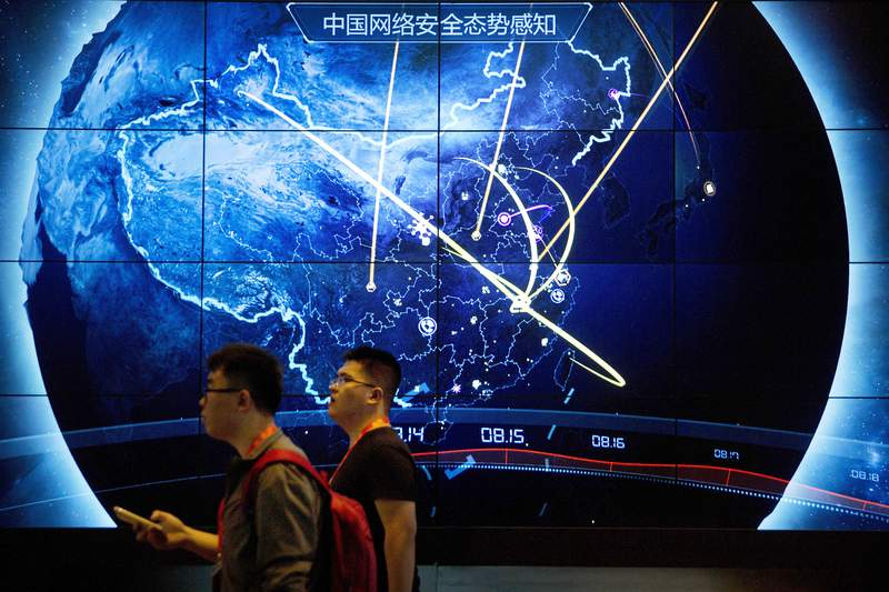 In this Sept. 12, 2017, file photo, attendees walk past an electronic display showing recent cyberattacks in China at the China Internet Security Conference in Beijing. Tech experts in China who find a weakness in computer security would be required to tell the government instead of publicizing it under rules announced Tuesday, July 13, 2021, as part of the ruling Communist Partys sweeping effort to tighten control over information. (AP Photo/Mark Schiefelbein, File)