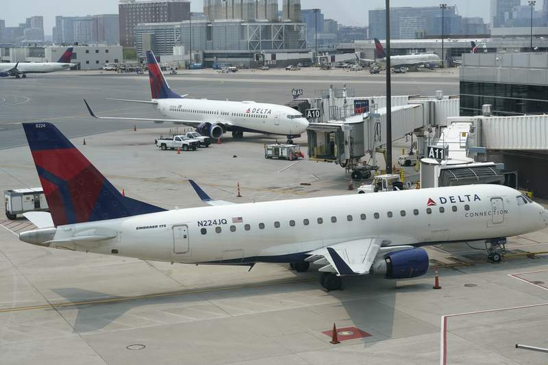 Delta Air Lines passenger jets rest on the tarmac, Wednesday, July 21, 2021, at Boston Logan International Airport, in Boston. Airlines say the current rise in new cases of coronavirus aren't scaring away travelers.    (AP Photo/Steven Senne)