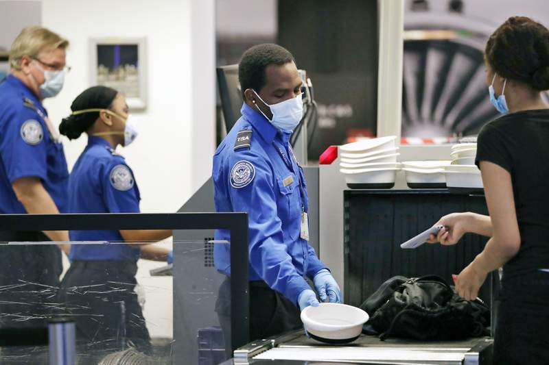 FILE - In this May 18, 2020, file photo, Transportation Security Administration officers wear protective masks at a security screening area at Seattle-Tacoma International Airport in SeaTac, Wash. The Biden administration says it is moving to increase the pay and union rights for security screeners at the nations airports. The Department of Homeland Security directed the acting head of the TSA to come up with a plan within 90 days to raise the pay of the screeners and expand their rights to collective bargaining.  (AP Photo/Elaine Thompson, File)