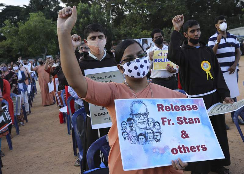 FILE- In this Nov.12, 2020 file photo, a Christian nun, center, holds a placard and shouts slogans with others demanding the release of tribal rights activist Stan Swamy and other activists during a demonstration in Bengaluru, India. Father Stan Swamy, a jailed Jesuit priest and longtime Indian tribal rights activist, has died at 84 of a cardiac arrest in the western Indian city of Mumbai. (AP Photo/Aijaz Rahi, File)