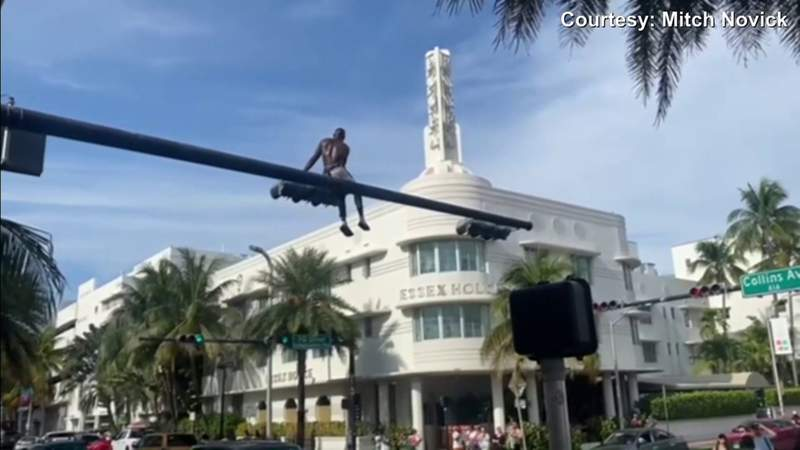 Man stops traffic on busy Collins Avenue when he climbs atop traffic light