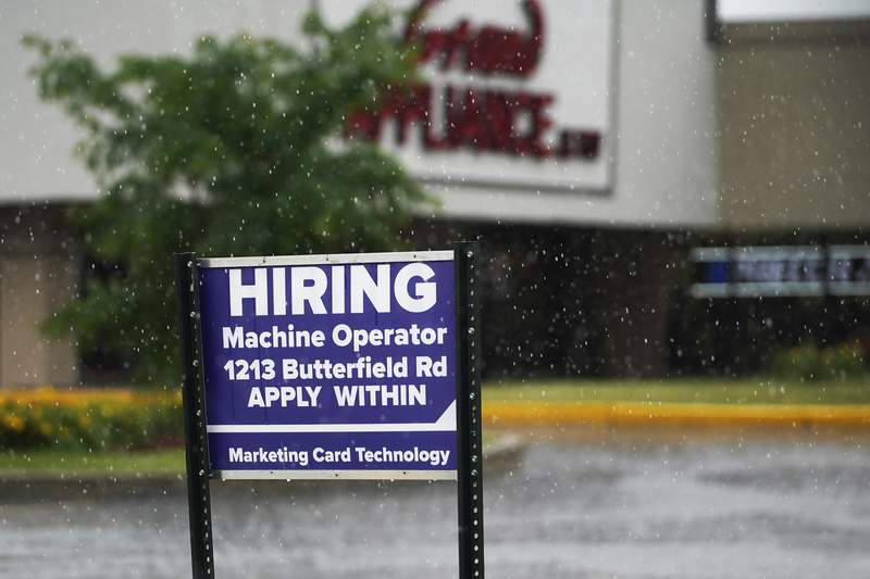 A hiring sign shows in Downers Grove, Ill., Thursday, June 24, 2021.  Pay is going up across many industries as the economy roars out of the recession. While that's good for workers, investors on Wall Street worry that a big and sustained gain would be a worse threat for inflation than the price spikes already seen for oil, lumber and other commodities.    (AP Photo/Nam Y. Huh)