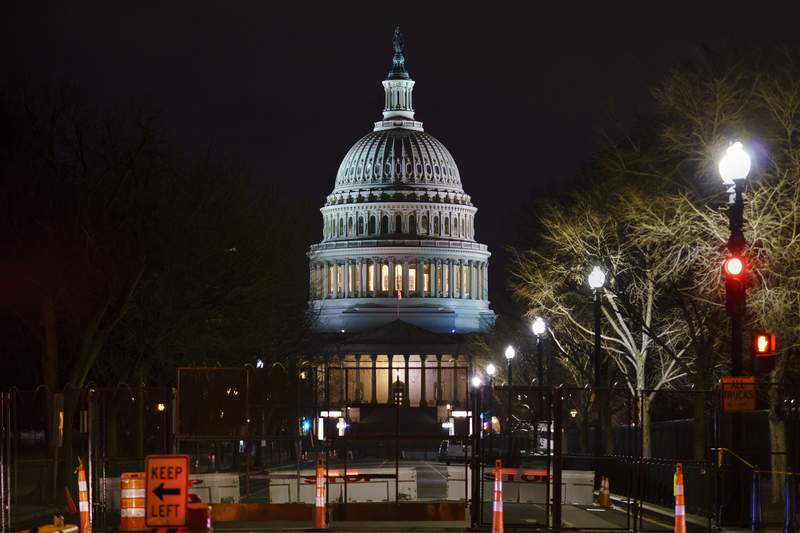 The Capitol is seen behind reinforced barricades as the second impeachment trial of former President Donald Trump begins in the Senate in Washington, Tuesday, Feb. 9, 2021.  (AP Photo/J. Scott Applewhite)
