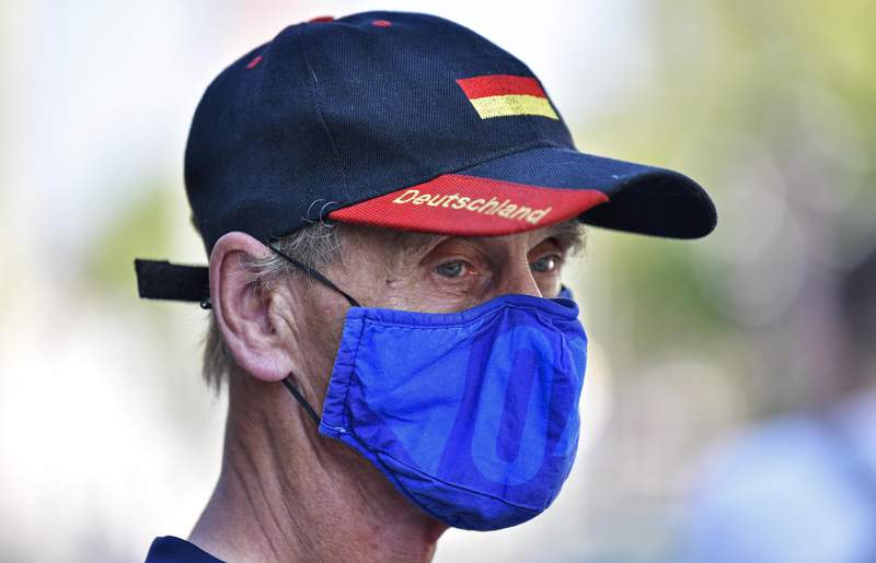 "Due to the new coronavirus pandemic a man wears a face mask of the German first division soccer team FC Schalke 04 and a hat with the word reading ""Deutschland"" (Germany) in Gelsenkirchen, Germany, Wednesday, Aug. 12, 2020. (AP Photo/Martin Meissner)"