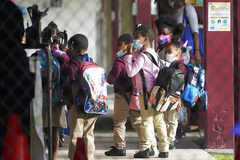 Children wait to enter classrooms, Monday, Oct. 5, 2020, at the Carrie P. Meek/Westview K-8 Center in Miami. (AP Photo/Wilfredo Lee)