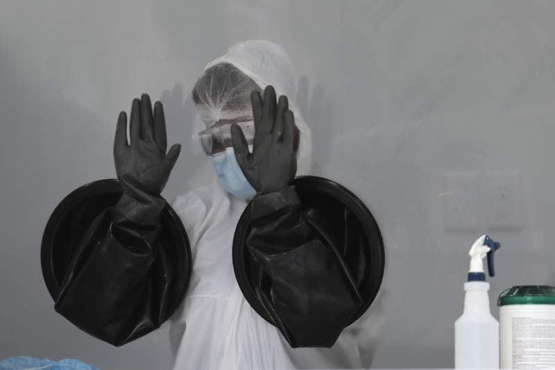 A healthcare worker air-dries her gloves after sanitizing her equipment while working at a walk-up COVID-19 testing site in Miami Beach. People getting tested are separated from nurses by a glass pane.