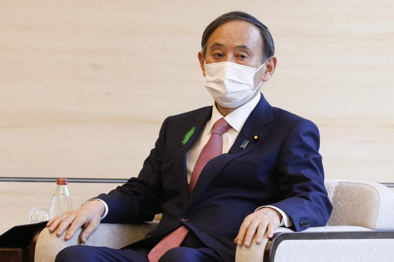 Japan's Prime Minister Yoshihide Suga wearing a face mask meets COP26 President Alok Sharma at the prime minister's official residence Monday, April 19, 2021, in Tokyo, Japan. (Rodrigo Reyes Marin/Pool Photo via AP)