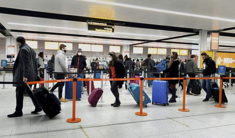 FILE - In this Dec. 20, 2020, file photo, passengers queue for check-in at Gatwick Airport in West Sussex, England, south of London. The United States will require airline passengers from Britain to get a negative COVID-19 test before their flight, the Centers for Disease Control and Prevention announced late Thursday, Dec. 24. The U.S. is the latest country to announce new travel restrictions because of a new variant of the coronavirus that is spreading in Britain. (Gareth Fuller/PA via AP)