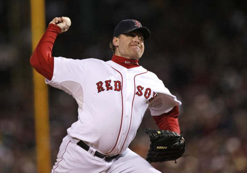 FILE - In this Oct. 25, 2007, file photo, Boston Red Sox's Curt Schilling pitches against the Colorado Rockies in Game 2 of the baseball World Series at Fenway Park in Boston. Like many baseball writers, C. Trent Rosecrans viewed the Hall of Fame vote as a labor of love. The results of the 2021 vote will be announced Tuesday, Jan. 26, 2021, and Rosecrans was not alone in finding the task particularly agonizing this time around. With Schilling's candidacy now front and center  and Barry Bonds and Roger Clemens still on the ballot as well  voters have had to consider how much a players off-field behavior should affect his Hall of Fame chances. (AP Photo/Kathy Willens, File)