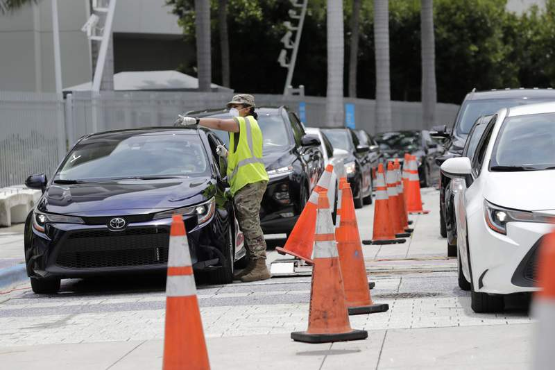 A member of the Florida National Guard monitors vehicles waiting in line outside of Marlins Park at a COVID-19 testing site during the coronavirus pandemic, Monday, July 6, 2020, in Miami. The long line of cars each morning as players arrive at work provides a reminder of the risks when they leave. Behavior away from the ballpark will be a big factor in determining whether Major League Baseball's attempt to salvage the 2020 season can succeed. (AP Photo/Lynne Sladky)
