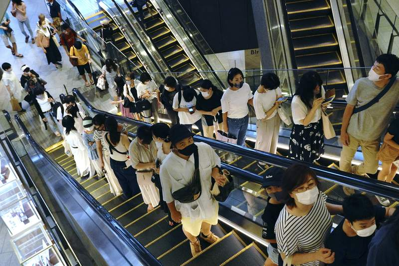 People take elevators at a shopping building in Tokyo on Aug. 24, 2020. Japanese manufacturers sentiments improved for the first time in three years, a quarterly Bank of Japan survey showed Thursday, Oct. 1, 2020, as the nation grappled with stagnation worsened by the coronavirus pandemic. (AP Photo/Eugene Hoshiko)