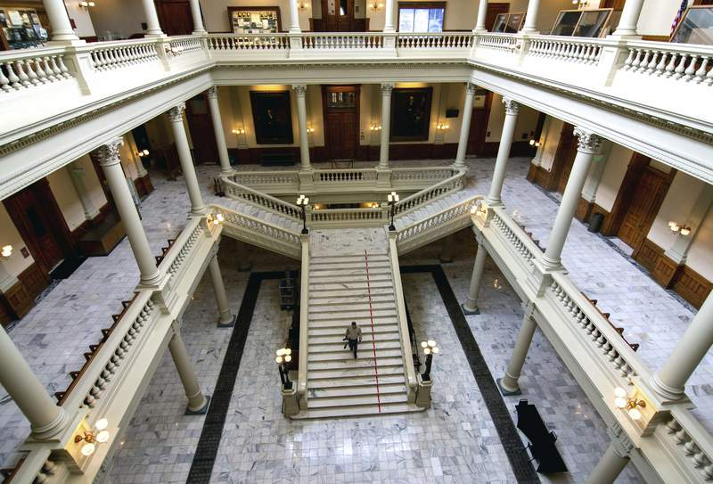 Travis Swann Taylor walks through a nearly empty Georgia State Capitol on Thursday, March 19, 2020, after Georgia lawmakers were urged Wednesday to self-isolate themselves, after a state senator said he tested positive for the coronavirus. (Steve SchaeferAtlanta Journal-Constitution via AP)