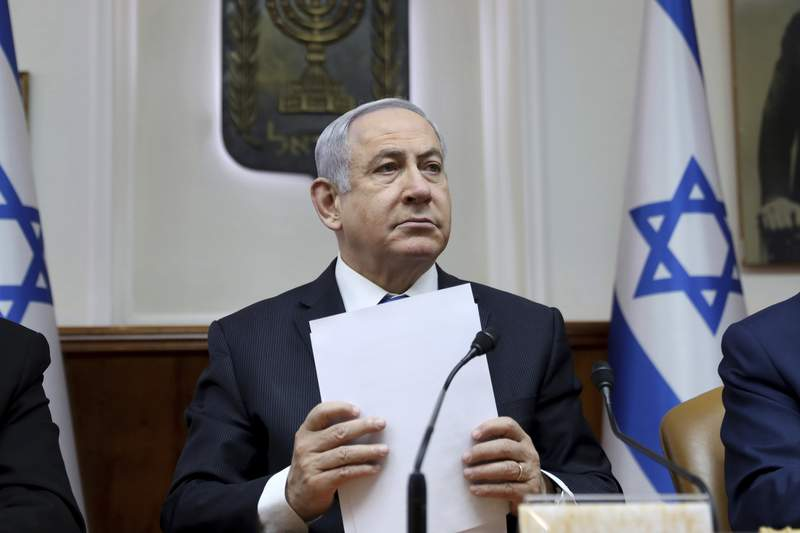 FILE - In this Feb. 16, 2020, file, photo, Israeli Prime Minister Benjamin Netanyahu chairs the weekly cabinet meeting, in Jerusalem. Several thousand Israelis have demonstrated Saturday, April 25, 2020 against a unity government deal reached last week that leaves Prime Minister Benjamin Netanyahu in power as he prepares to go on trial for corruption charges. The protesters say the unity government agreement crushes democracy and is meant to rescue Netanyahu from his legal troubles. (Gali Tibbon/Pool via AP, File)