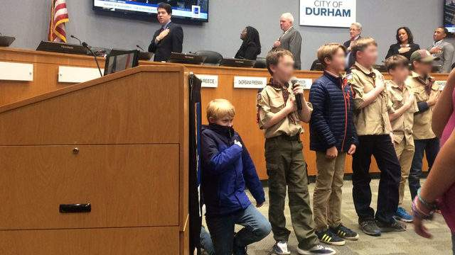 Cub Scout, 10, kneels for Pledge of Allegiance at council meeting