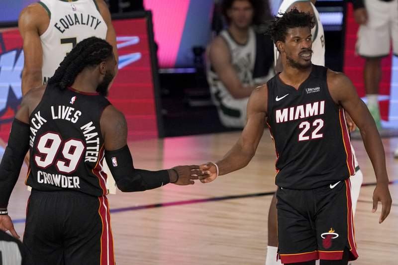 Miami Heat's Jae Crowder (99) and Jimmy Butler (22) celebrate their 104-115 win against the Milwaukee Bucks during an NBA basketball conference semifinal playoff game, Monday, Aug. 31, 2020, in Lake Buena Vista, Fla. (AP Photo/Mark J. Terrill)