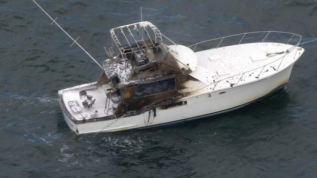 A view from Sky 10 shows the charred boat floating in the water.