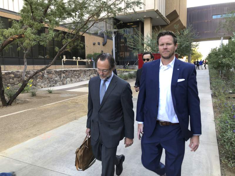 FILE - In this Nov. 5, 2019 file photo, former Maricopa County Assessor Paul Petersen, right, with his attorney, Kurt Altman, leave after a court hearing in Phoenix. Petersen, who admitted running an illegal adoption scheme in three states involving women from the Marshall Islands, was sentenced in Arkansas to six years in federal prison on Tuesday, Dec. 1, 2020. It was the first of three punishments hell face for arranging adoptions prohibited by an international compact. (AP Photo/Jacques Billeaud, File)