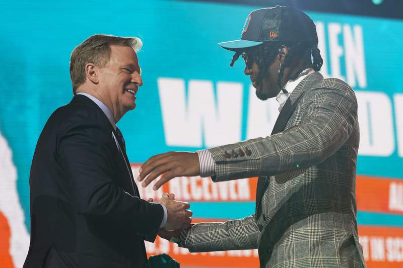 Alabama wide receiver Jaylen Waddle, right, greets NFL Commissioner Roger Goodell after being chosen by the Miami Dolphins with the sixth pick in the NFL Draft Thursday April 29, 2021, in Cleveland.